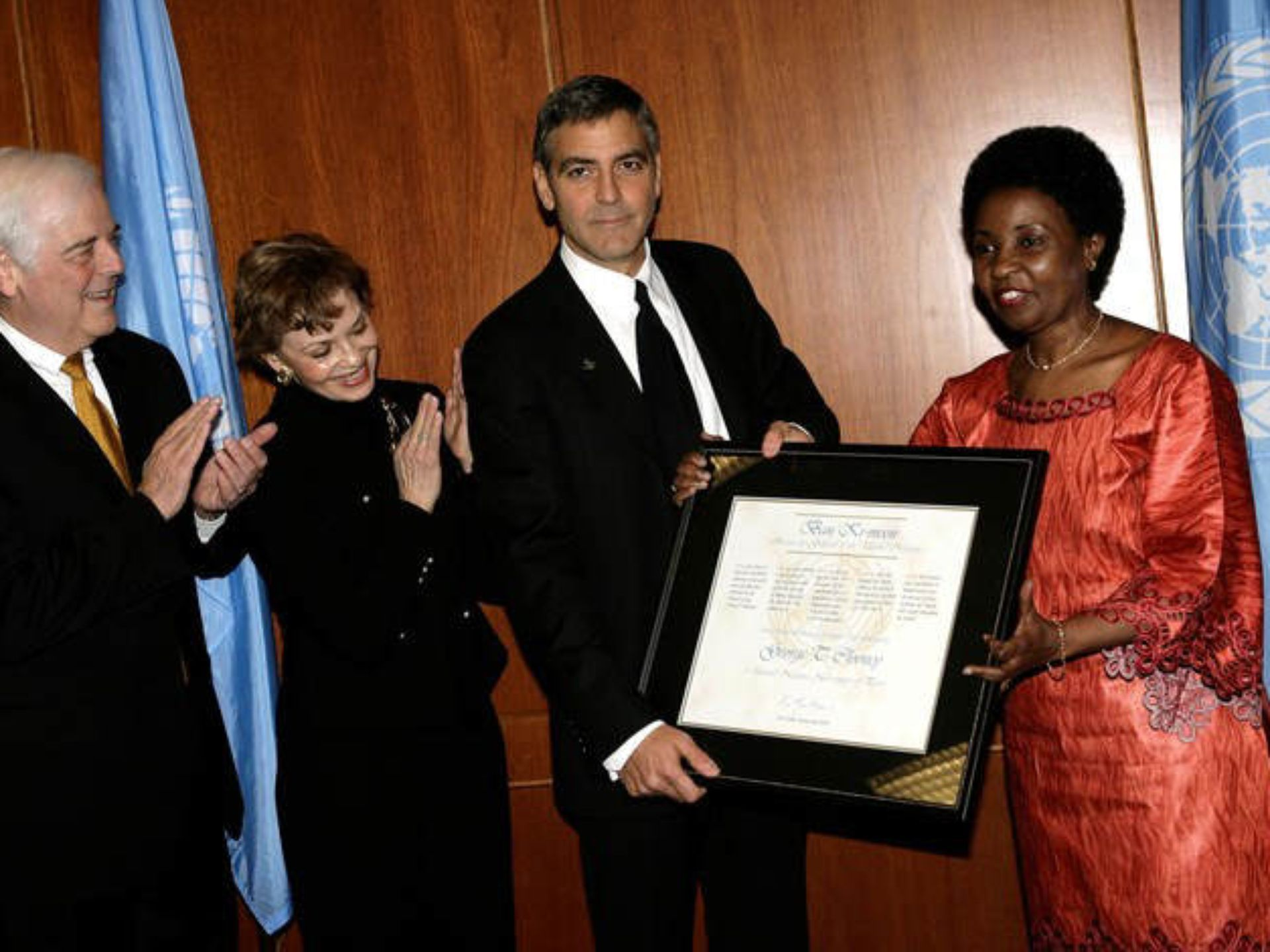 Deputy Secretary-General Dr. Asha-Rose Migiro, right, presents actor George Clooney, second from right, with a certificate to honor his new role as a United Nations Messenger of Peace at U.N. headquarters. Clooney's mother, Nina Clooney, and father, Nick Clooney, left, look on.