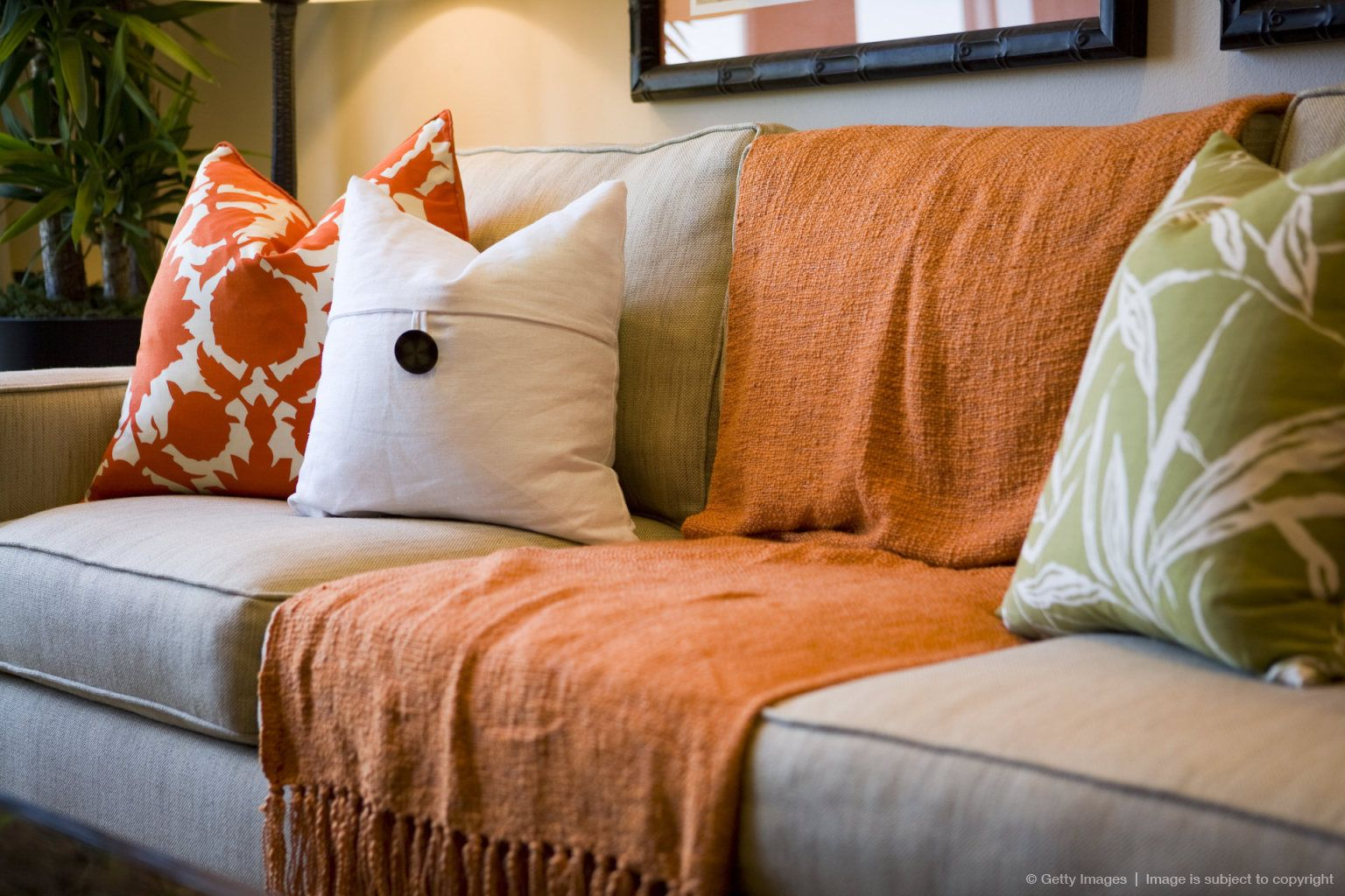 Comfortable Sofa With Orange Throw Blanket And Decorative