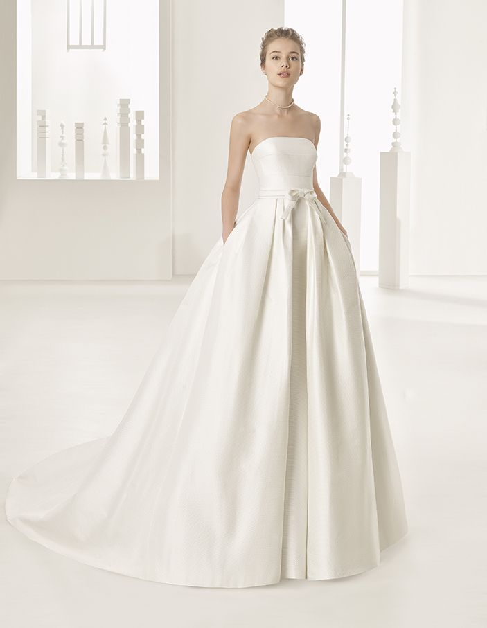 Naroa - Pleated silk piqué strapless column dress and overskirt with hemstitch details on bow at waist and parts of dress, in natural.