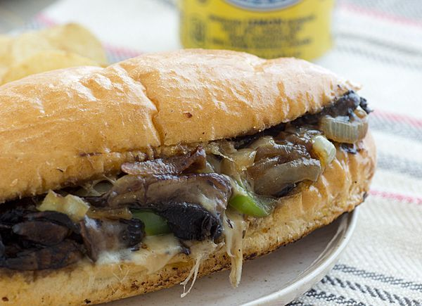 Mushroom Cheesesteaks 2 tbsp. olive oil, divided *2 extra-large portabella mushrooms, thinly sliced *2 tbsp. red wine *salt + pepper to taste *1 small green pepper, thinly sliced *1 large onion, thinly sliced   8 slices provolone or mozzarella cheese *4 sub rolls, sliced lengthwise (don't completely cut the top from the bottom, t