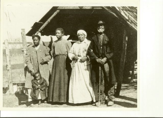 "A picture showing five generations at Mosby Hall in Littleton, the home of John Pelopidus Leach after the war. From right to left, ""Uncle Essex, Aunt Emily, Aunt Agnes, and Aunt Mabel [with her child whose name author does not know]. This was probably taken around 1900. Notice the Confederate Great Coat that Aunt Mabel is wearing. Uncle Essex was born a slave, and lived in ""Person's Ordinary"" on Mosby Hall Plantation where he was a stage coach driver."""