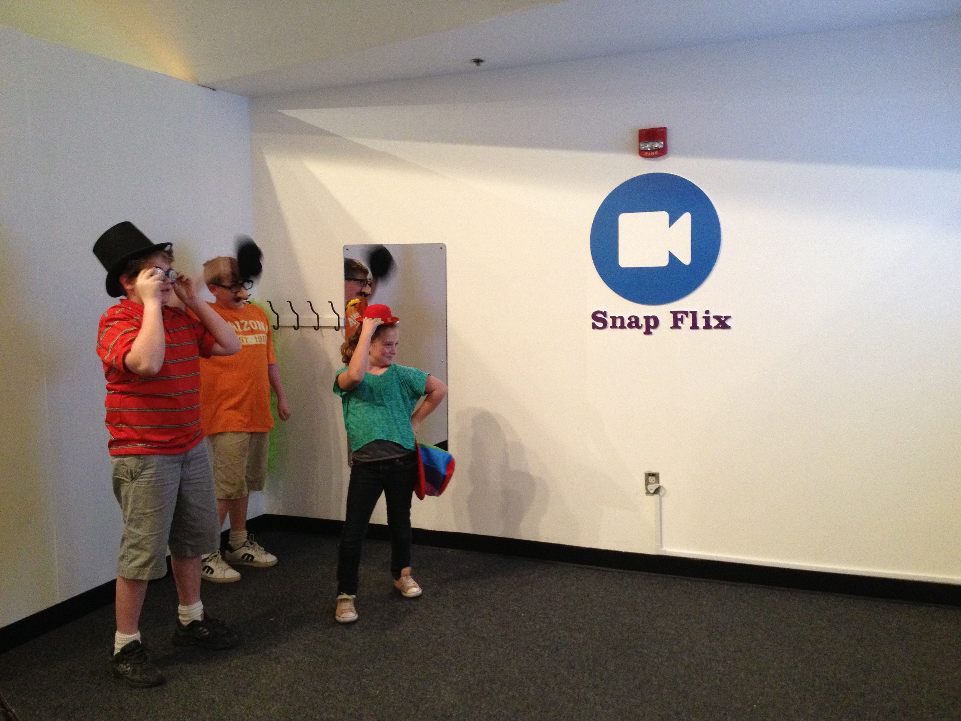 kids at the snap flix booth where they can record movies while in