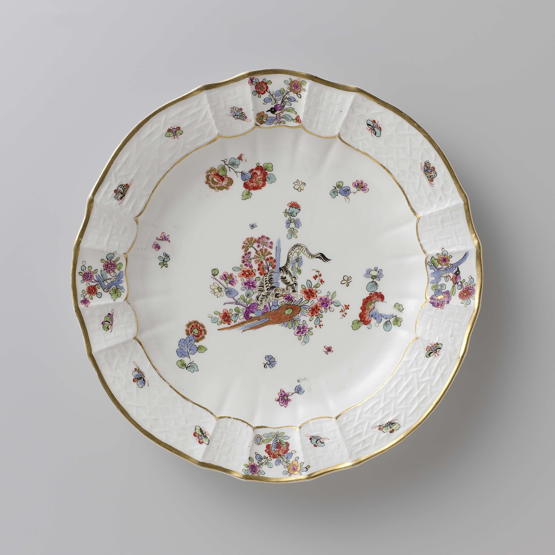 Meissener Porzellan Manufaktur   Rond bord, veelkleurig beschilderd met een Kakiemon-decor, Meissener Porzellan Manufaktur, c. 1740 - c. 1745   Rond bord van beschilderd porselein. Het bord is geribd en heeft een geschulpte rand. Het bord is beschilderd met een tijger die om een blauwe bamboestengel tussen bloemen is gedraaid, gestrooide Indianische Blumen, vlinders en takken waarop vogels. De rand is versierd met het 'Altbrandenstein'-patroon. Het bord is gemerkt.