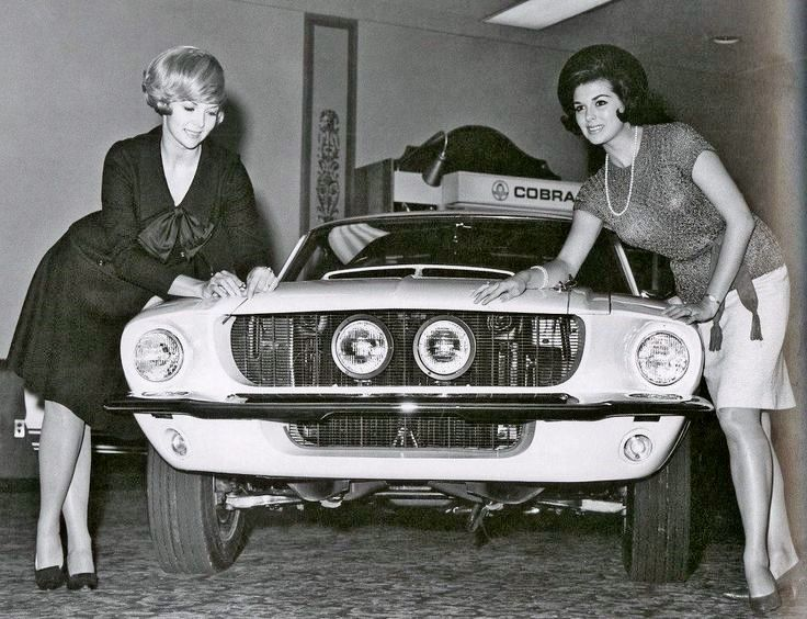 1960s shelby mustang in showroom and two lovely ladies