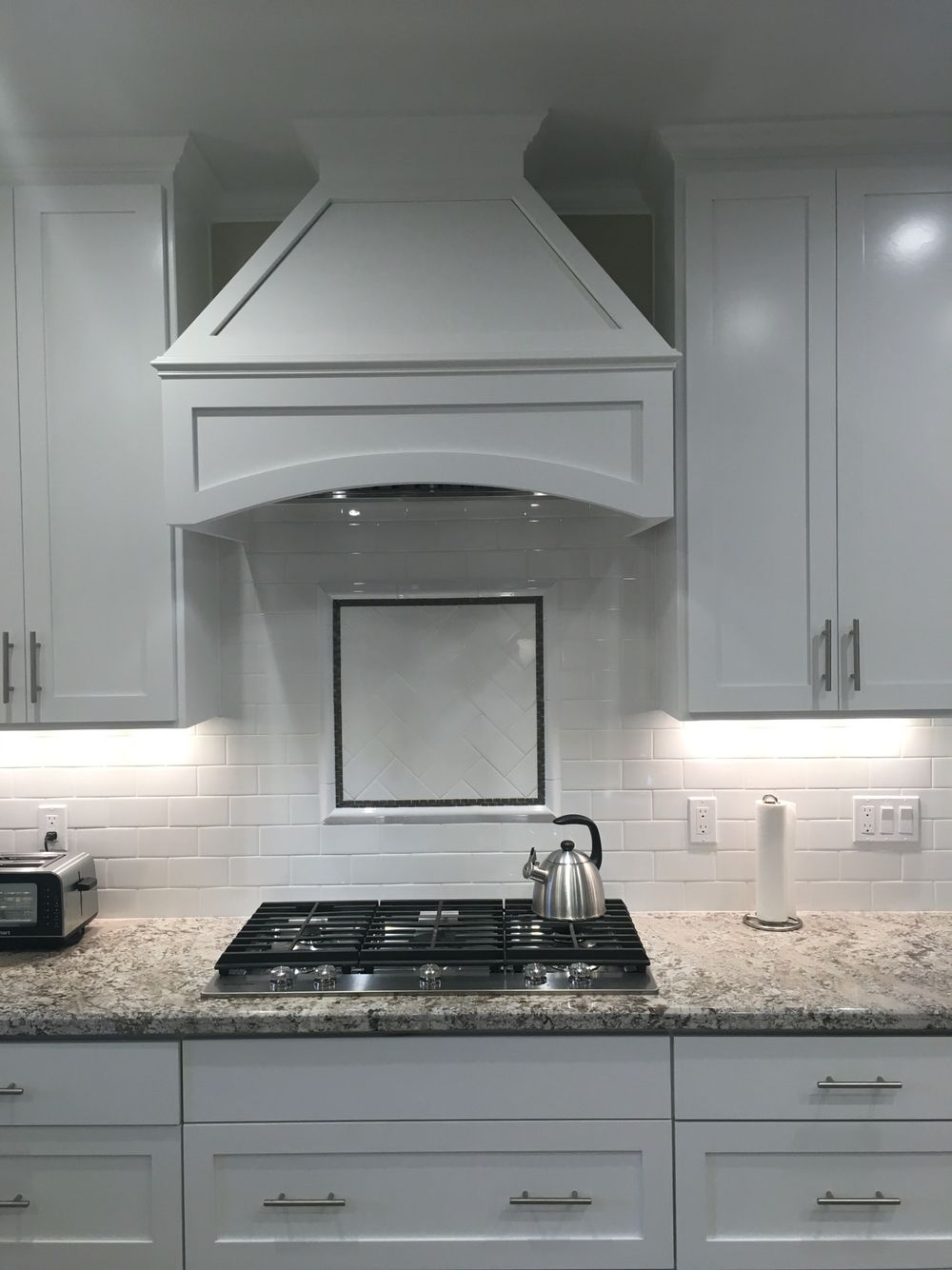 white kitchen. Backsplash stove design. Bianco Antico granite with subway tile backsplash.