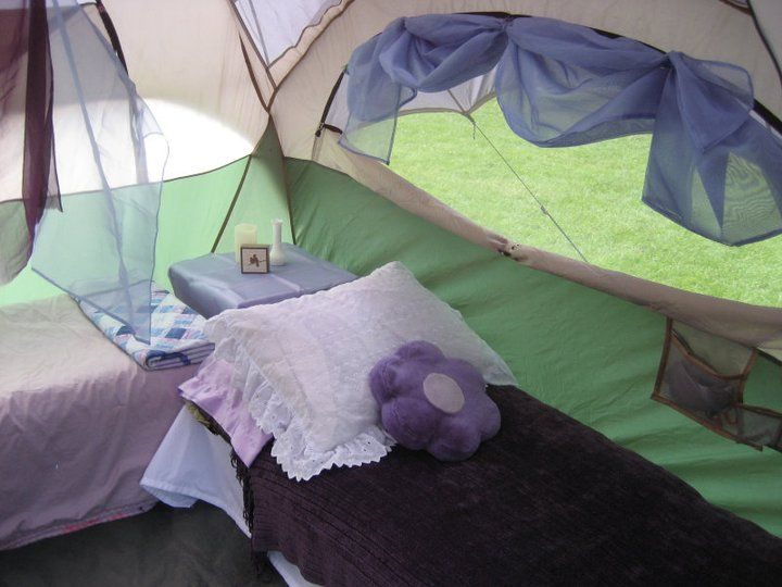 """Tent Decor. Sheets from Goodwill cover cots to the floor of the tent and give us a spot to store our """"stuff."""" Extra strips of fabric can be clipped around the windows to make """"valances"""". I love having a nightstand. It is a table that folds flat."""