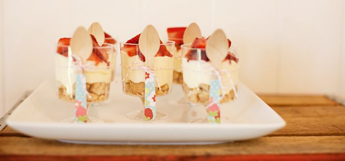 strawberry dessert table: strawberry shortcake parfaits with wooden spoons covered with printable paper {styling + printables by Hello Love Designs}