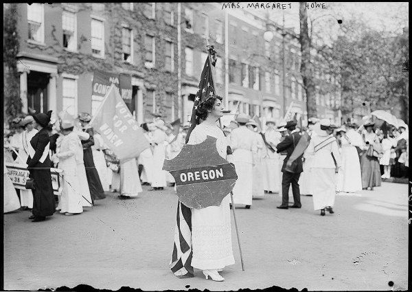 """Margaret Howe holding an """"Oregon"""" shield in Washington D.C. at a women's suffrage march in 1913. Oregon women obtained the right to vote in 1912."""