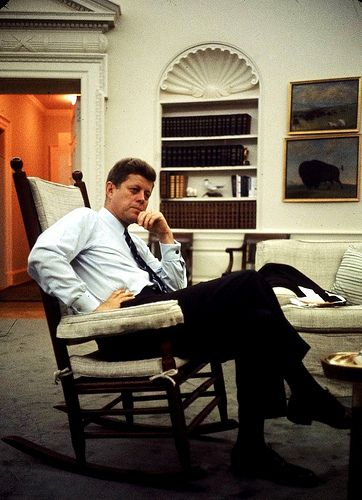 pres john f kennedy sitting in rocking chair in his