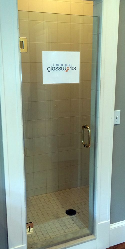 Very simple clear frameless swinging shower door with polished brass ...