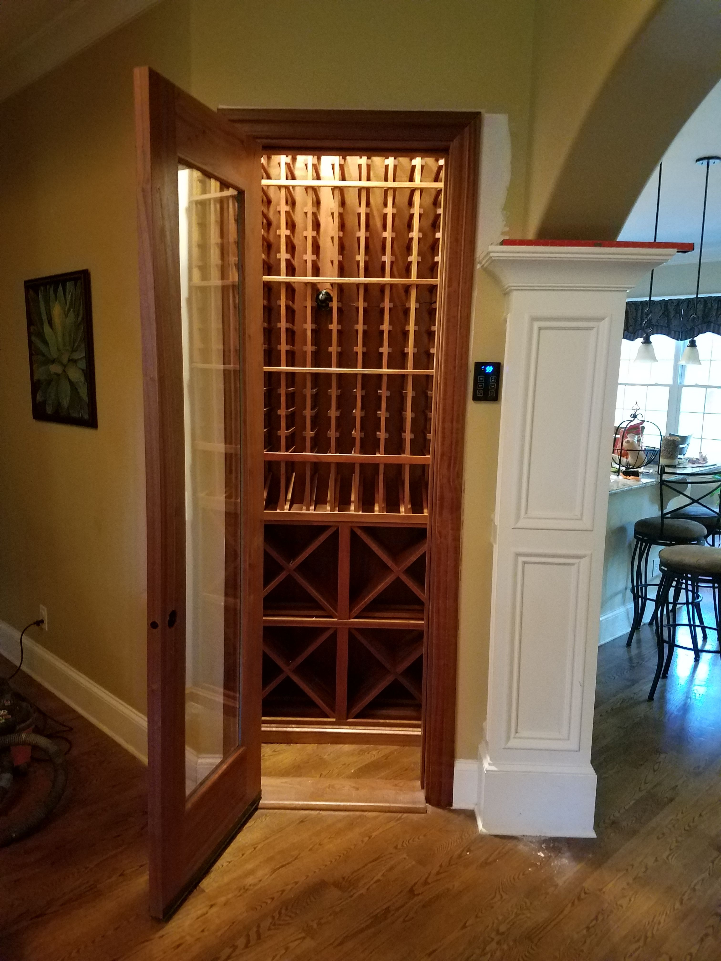 Closet converted into a climate controlled cellar. Wine