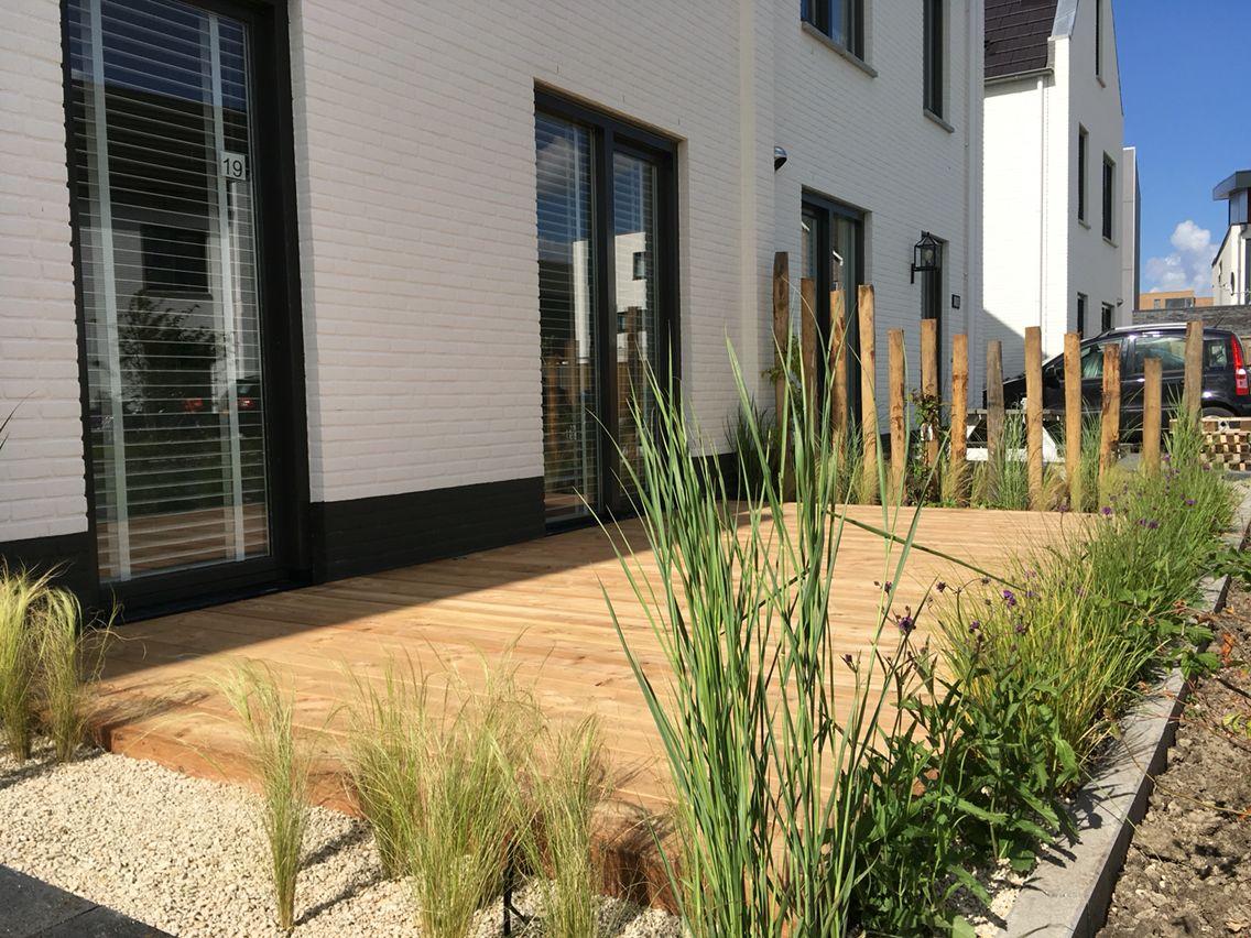 Houten terras in de voortuin met kastanje palen en siergrassen hovenierjordinrozendaal - Terras hout ...