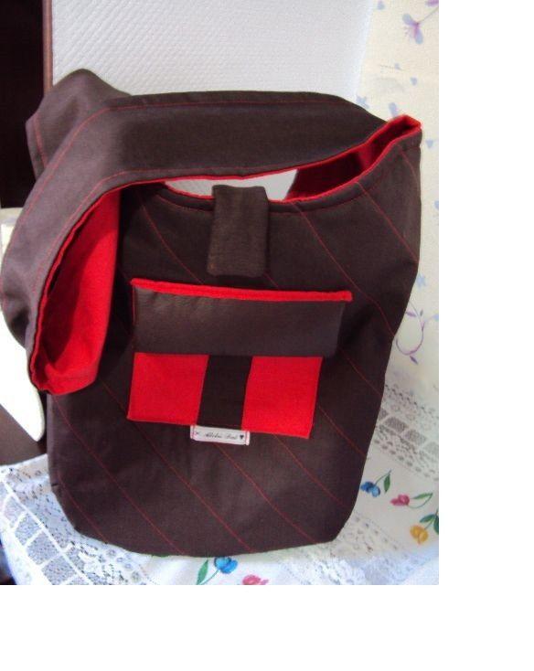 Bolsa em tecido brim com detalhes em couro. Forrada e com bolso externo e interno.
