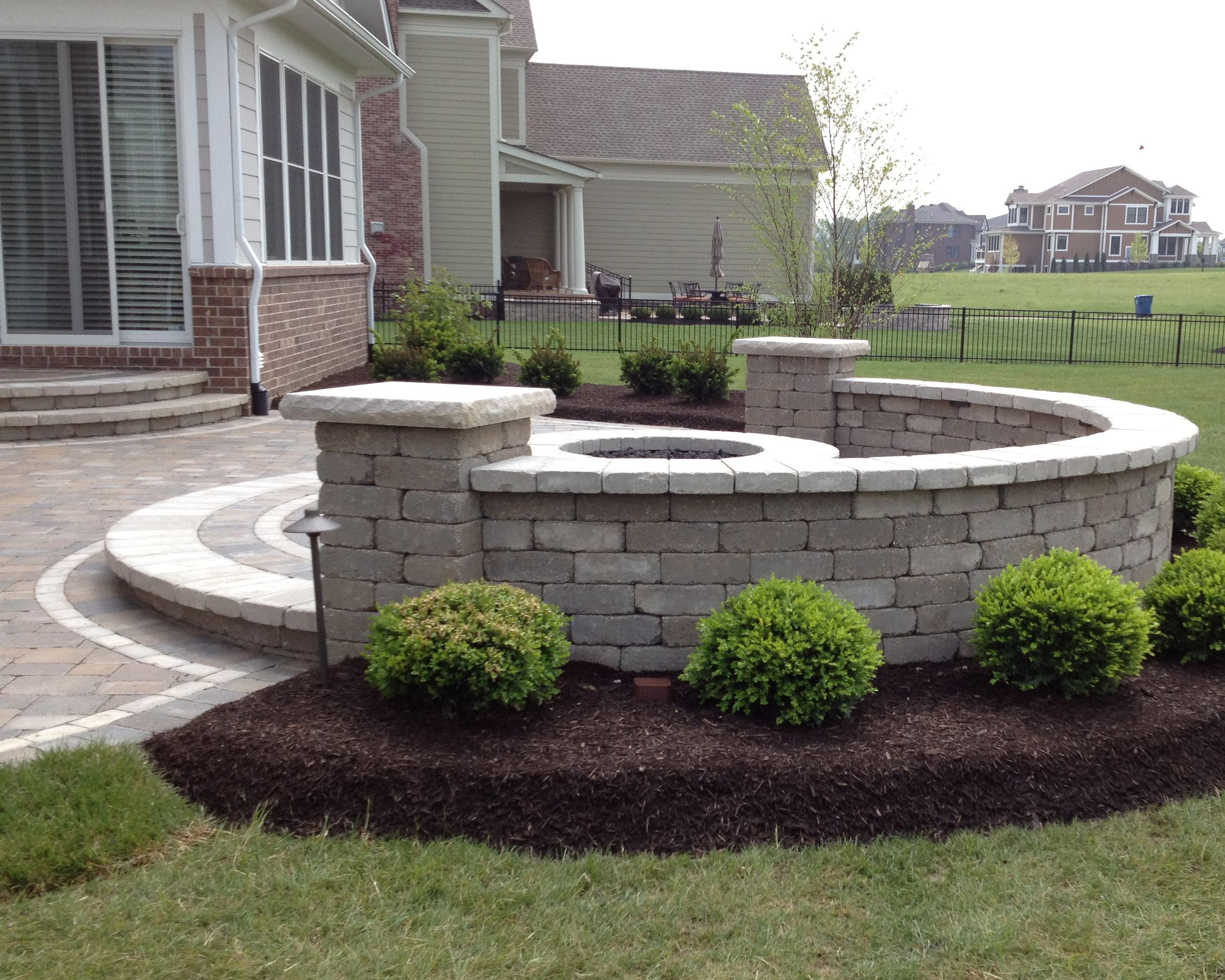 raised patio with seat wall and firepit installed by brick paving of indianapolis - Raised Patio Ideas