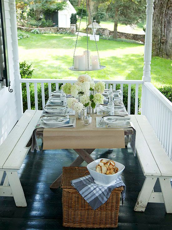 On This Small Porch A Slim Folding Table Is Paired With White Wooden Benches That Allow For Several People To Share Meal