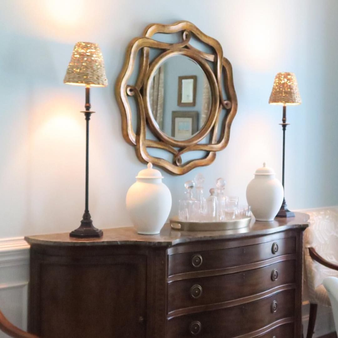 Round Mirror In Dining Room, Buffet Lamps, Pale Blue Walls.