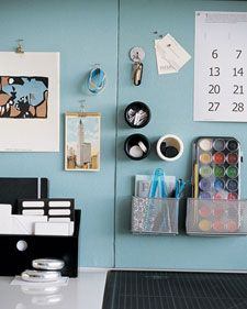 Cover alternating panels of bulletin and magnetic board in unifying swaths of linen to create a functional backdrop. Magnetic hooks, caddies, and tins provide hanging storage for small items.