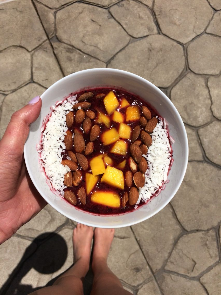 Berry bowl  Put 1 and a half handfuls of frozen berries and 1 cup coconut water in blender. Blend. If you want the consistency to be thicker add ice cubes or vanilla yogurt. Pour mixture in bowl and add toppings you wish. I choose coconut shreds, almonds, and mango. Enjoy!!