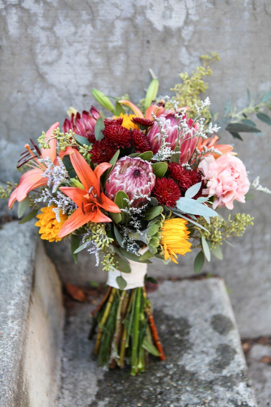 Rustic Wedding Bouquet Made With Protea Mini Sunflowers Orange Lilies Carnations Burgundy Button M Rustic Wedding Bouquet Protea Wedding Eucalyptus Bouquet