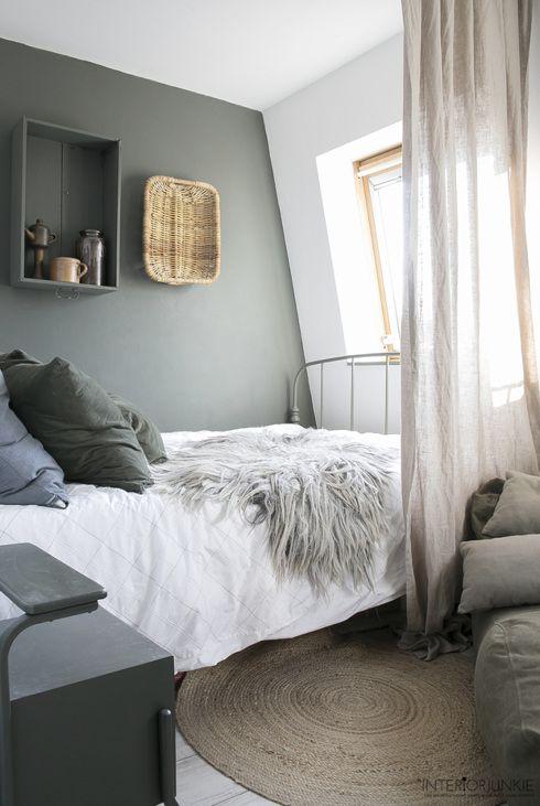 Slaapkamer met wit dekbedovertrek, grijsgroene muur en jute vloerkleed