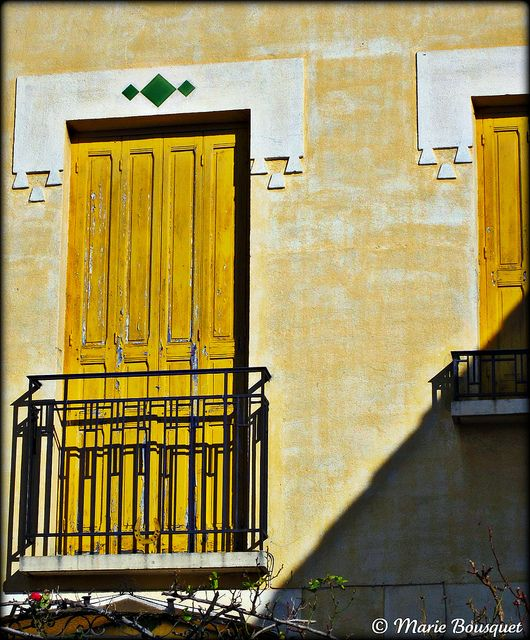 Porte-fenêtre au volet jaune avec balcon Spaces
