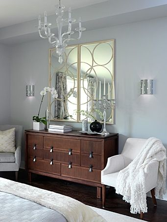 A beautiful transitional master #bedroom design from Sarah Richardson with a gorgeous dresser, glam chandelier and two white side chairs