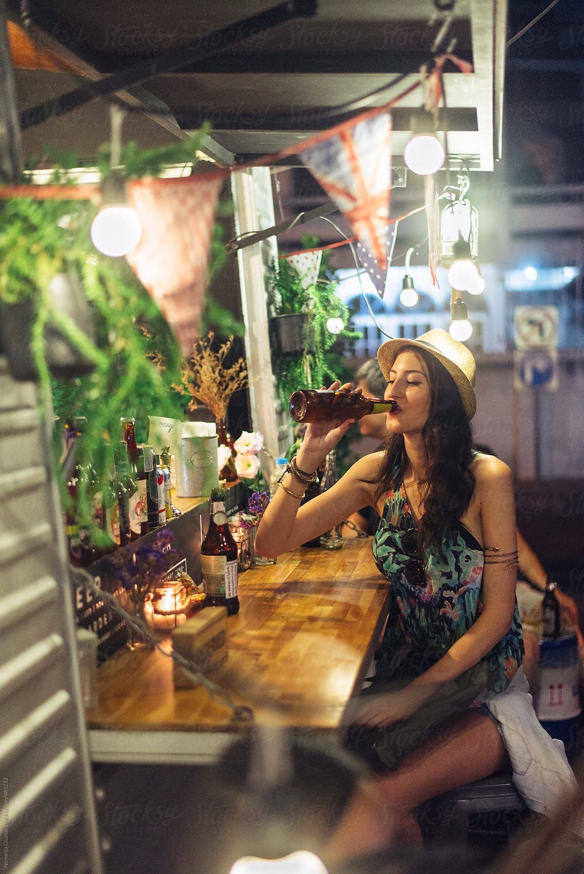 Carefree beautiful caucasian woman drinking beer at the