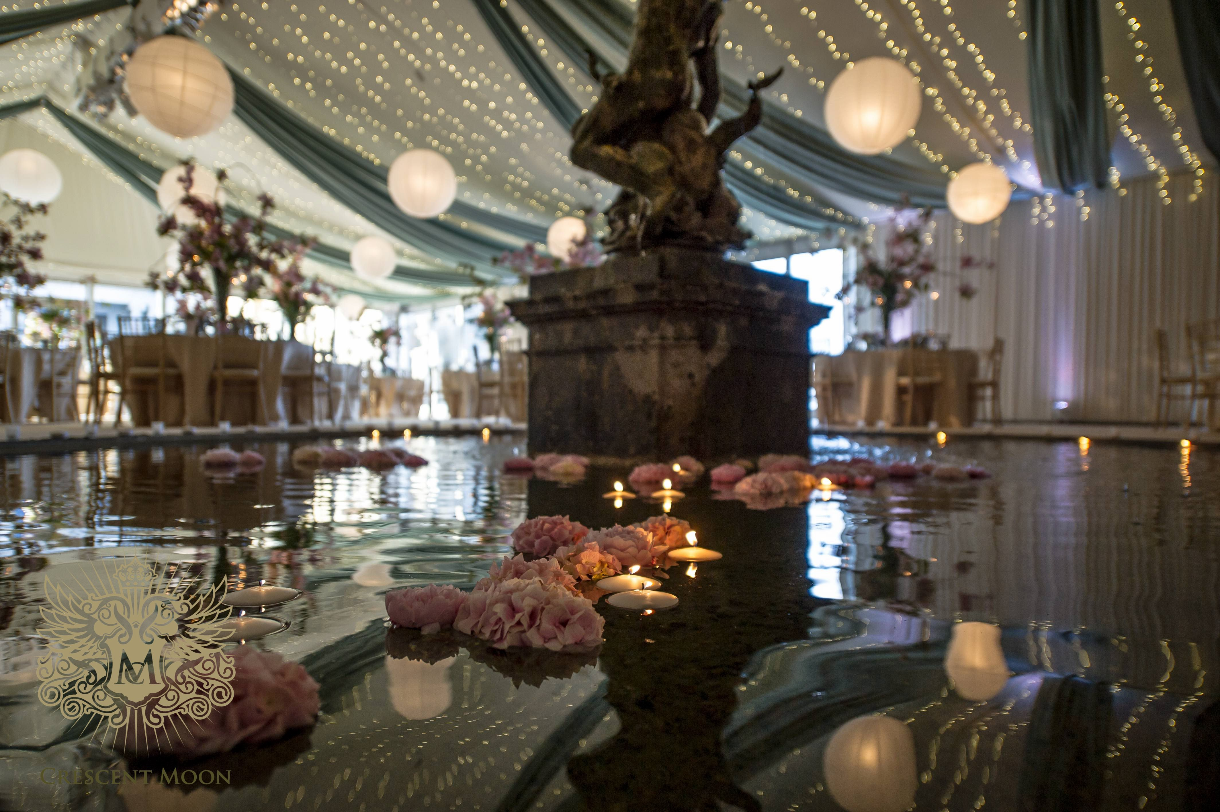 A marquee built over and around a fountain, with fairy lights, draping and lanterns
