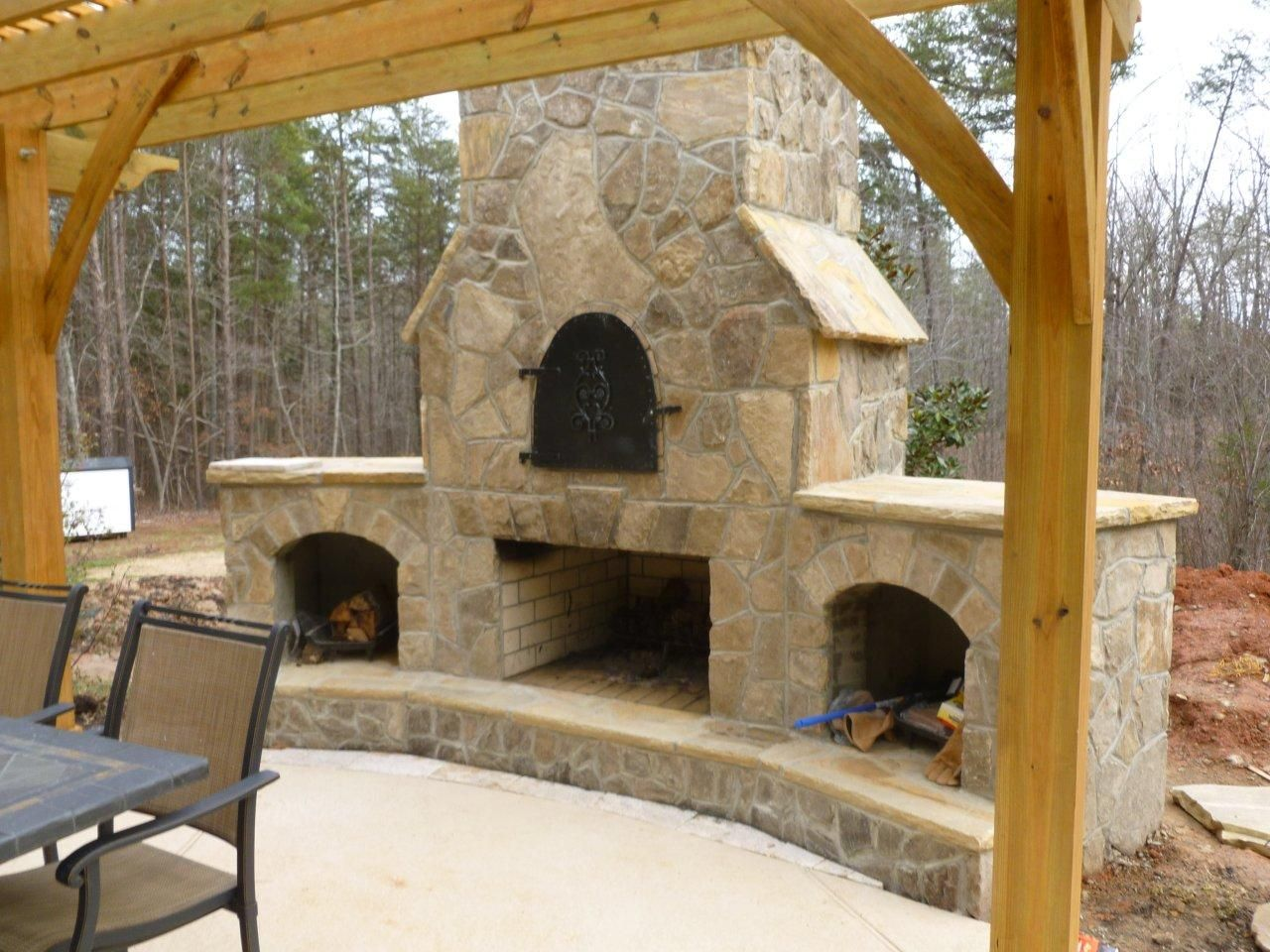 stone outdoor fireplace with a stone pizza oven and dry storage
