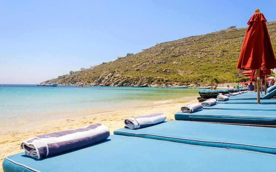 Psarou Beach, Mykonos: This beach embraces Mykonos' hedonistic, see-and-be-seen vibe. In the peak summer months, this sheltered cove is chock-a-block with blue loungers—and partygoers ordering magnums of rose from the pricey Nammos restaurant, dancing to club tunes while they swim.