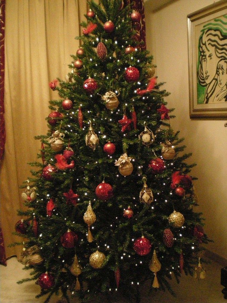 adornos preciosos de color oro y rojo en el rbol de navidad