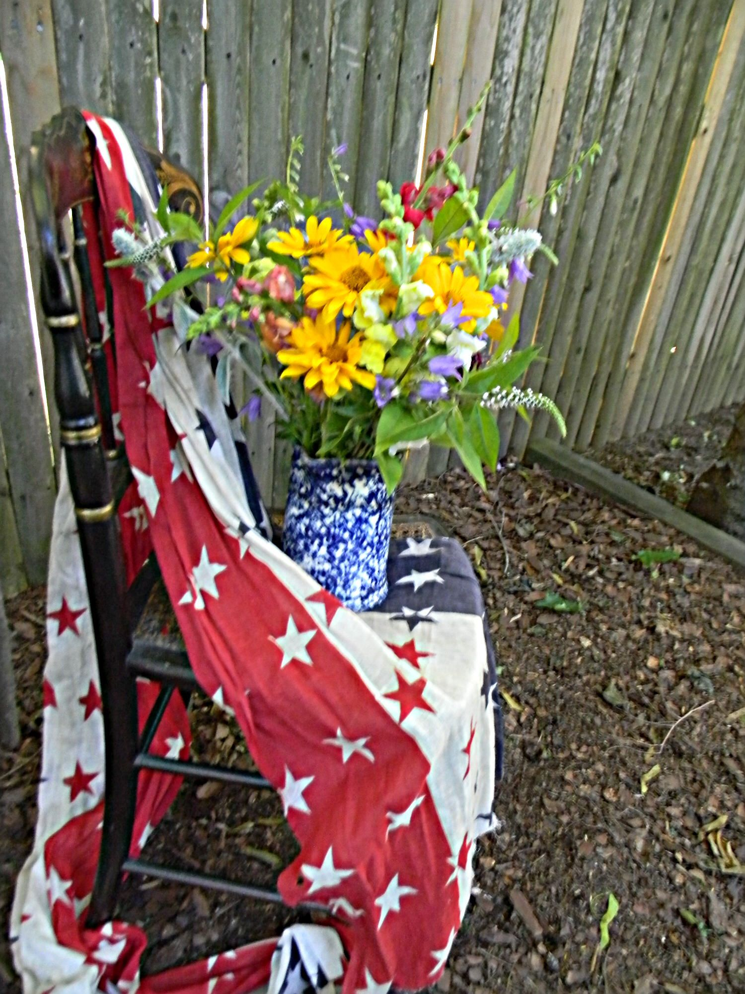 Summer bouquet arranged in a blue spongeware pitcher.  We added red, white and blue bunting and displayed them on an antique lady's chair.