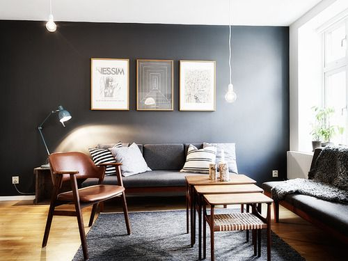 The colors of dark grey wall, light brown floor and dark brown furniture  work to