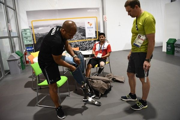 Peruvian's athletes Carlos Felipa Cordova (L) and Jose Luis Casas test their legs at the Ottobock workshop in charge of reparing prosthesis at the athletes village, during the Paralympic Games in Rio de Janeiro, Brazil on September 10, 2016. / AFP / CHRISTOPHE SIMON