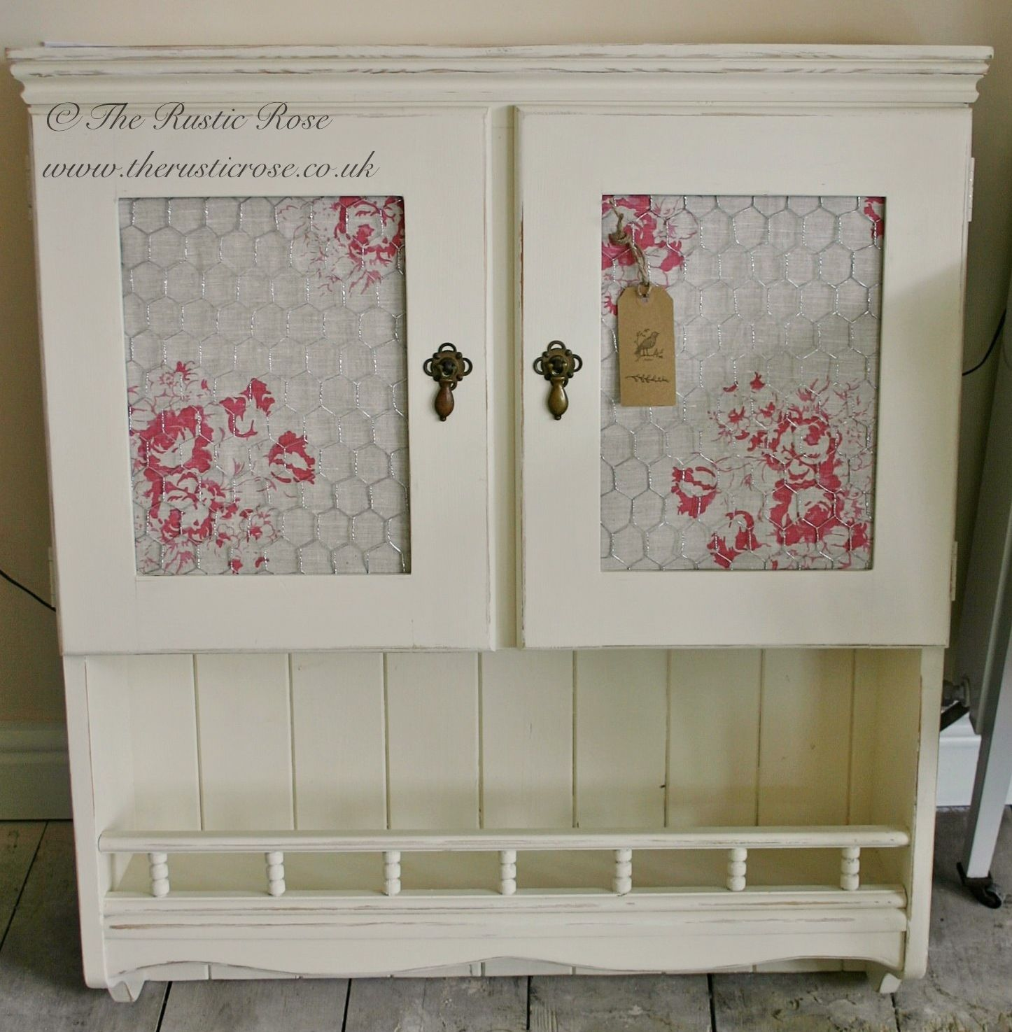 Wall cabinet with cabbages and roses fabric behind chicken wire guest bath storage
