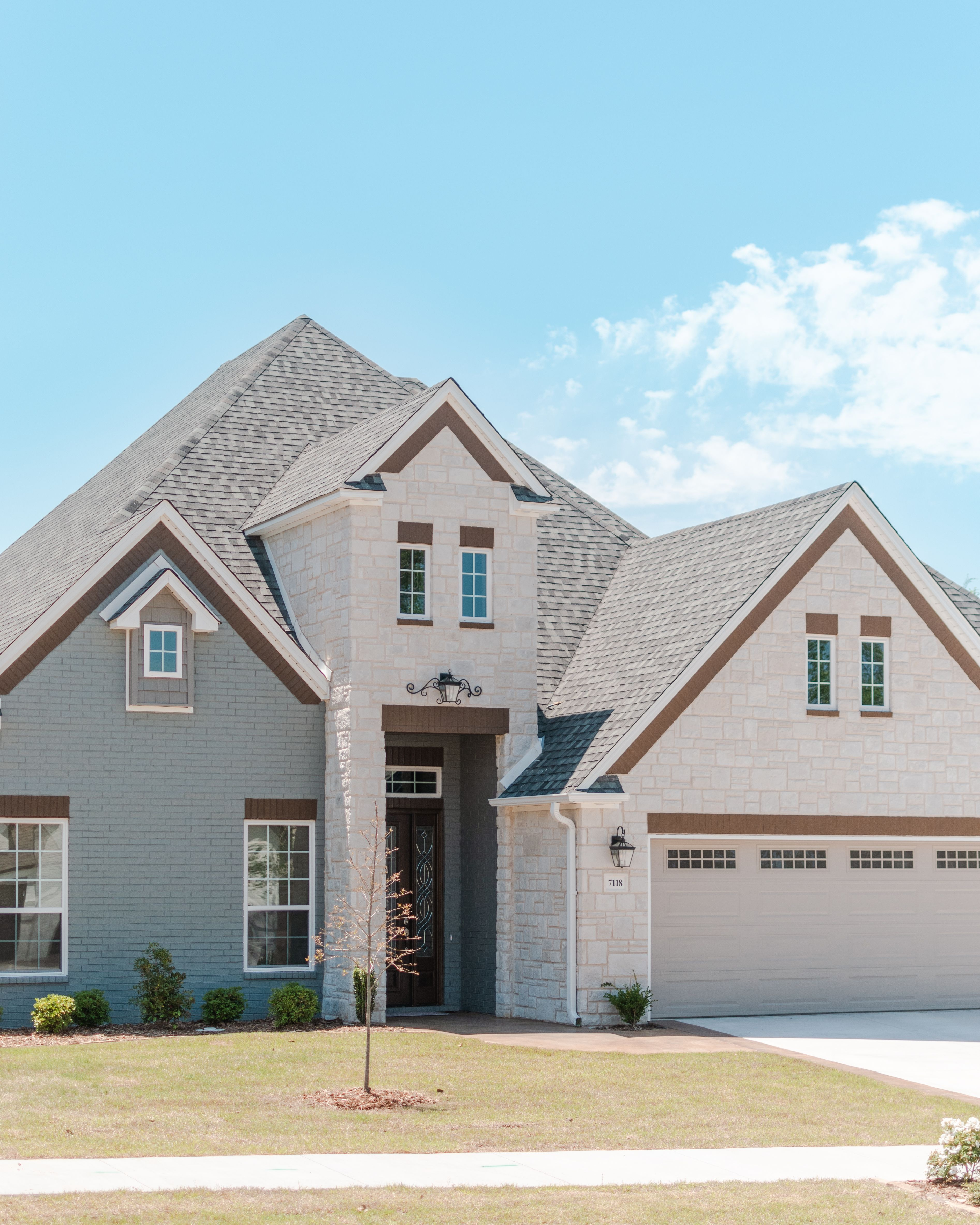 Gray Painted Brick Home Featuring White Rock With Weatherwood Roofing Dark Brown Headers And Trim