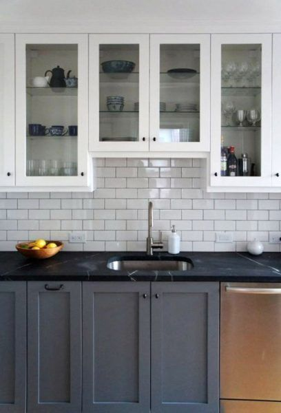 Two tone kitchen cabinets with black countertops