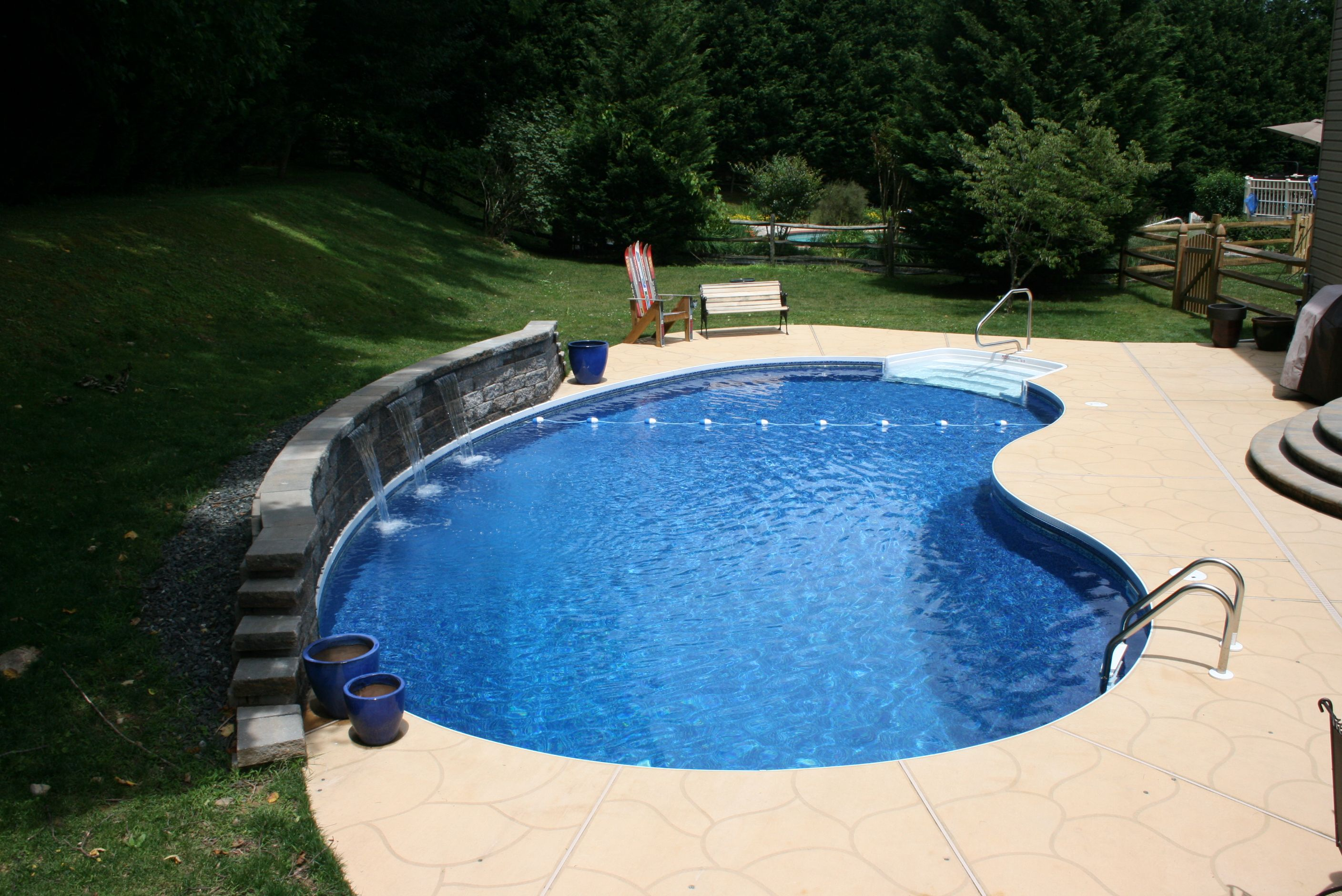 Waterfalls in the retaining wall make this kidney shaped for Kidney shaped pool designs
