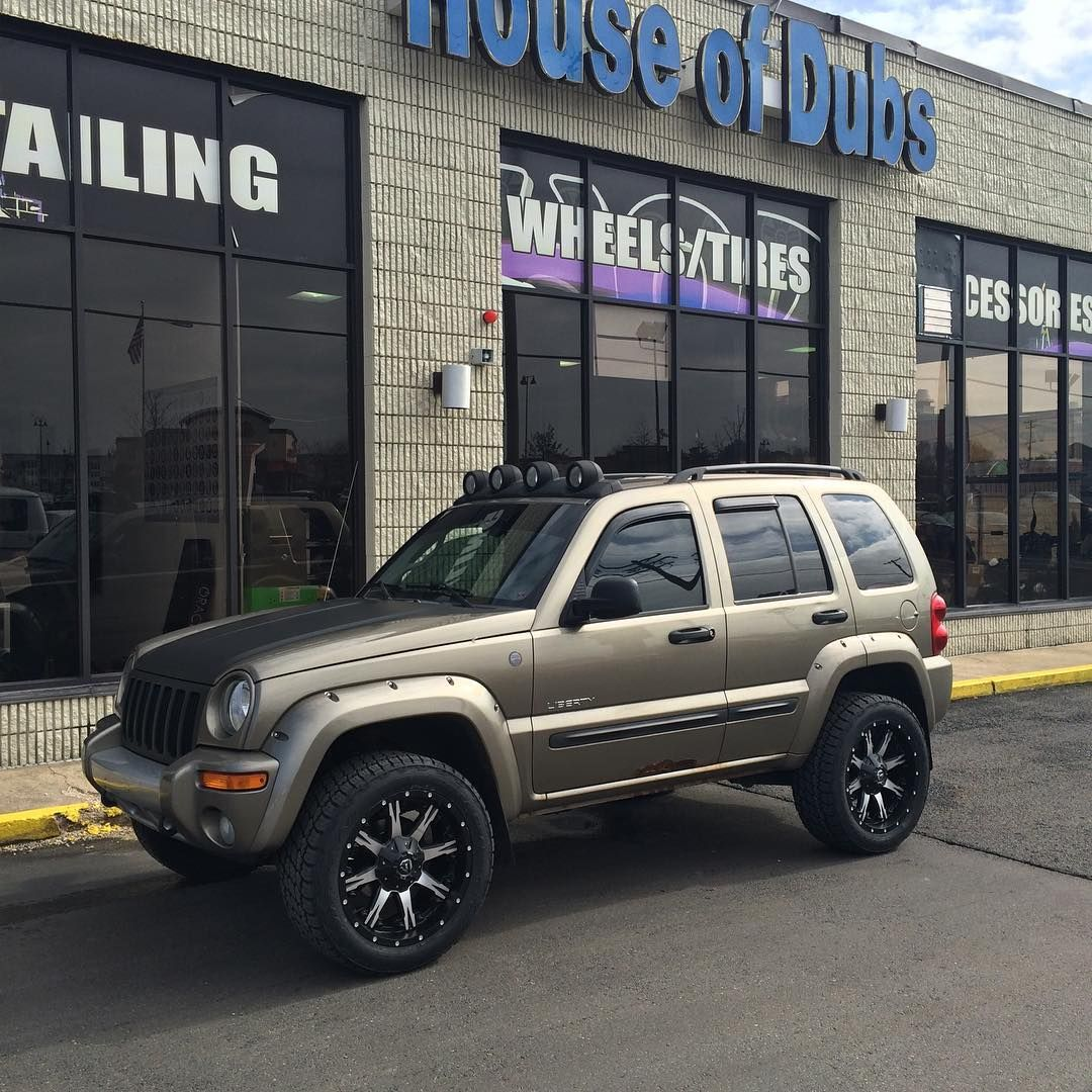 Jeep liberty with wrapped matte black grill and hood lifted on 20 fueloffroad wheels