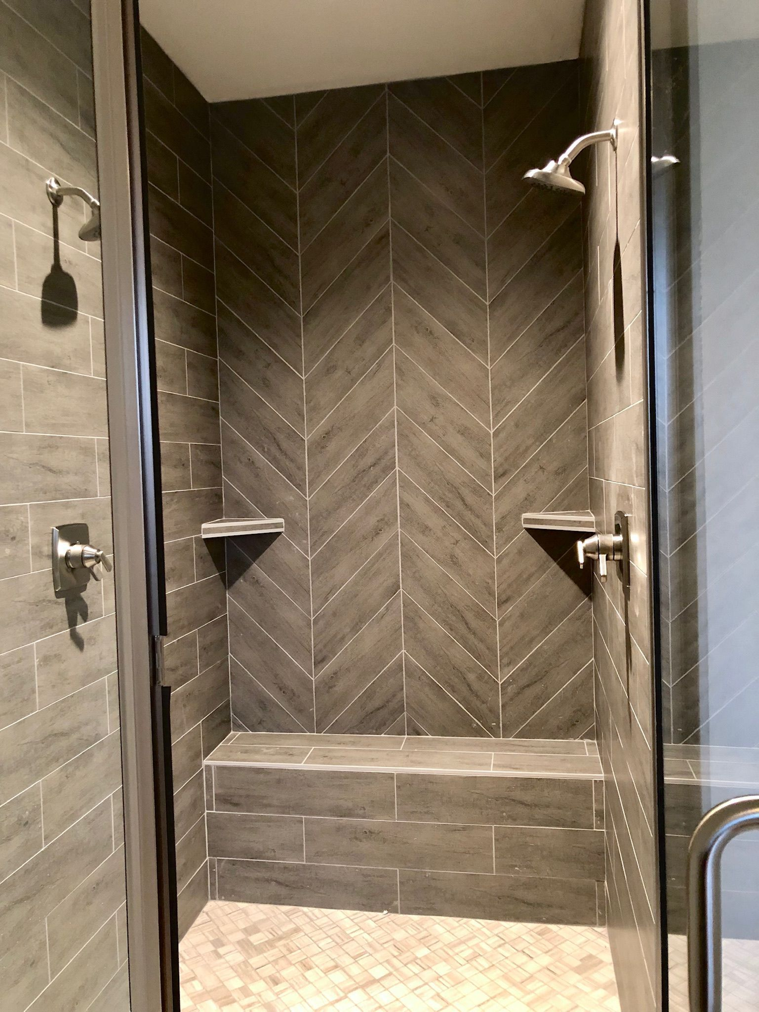 Custom gray herringbone tiled shower with double shower