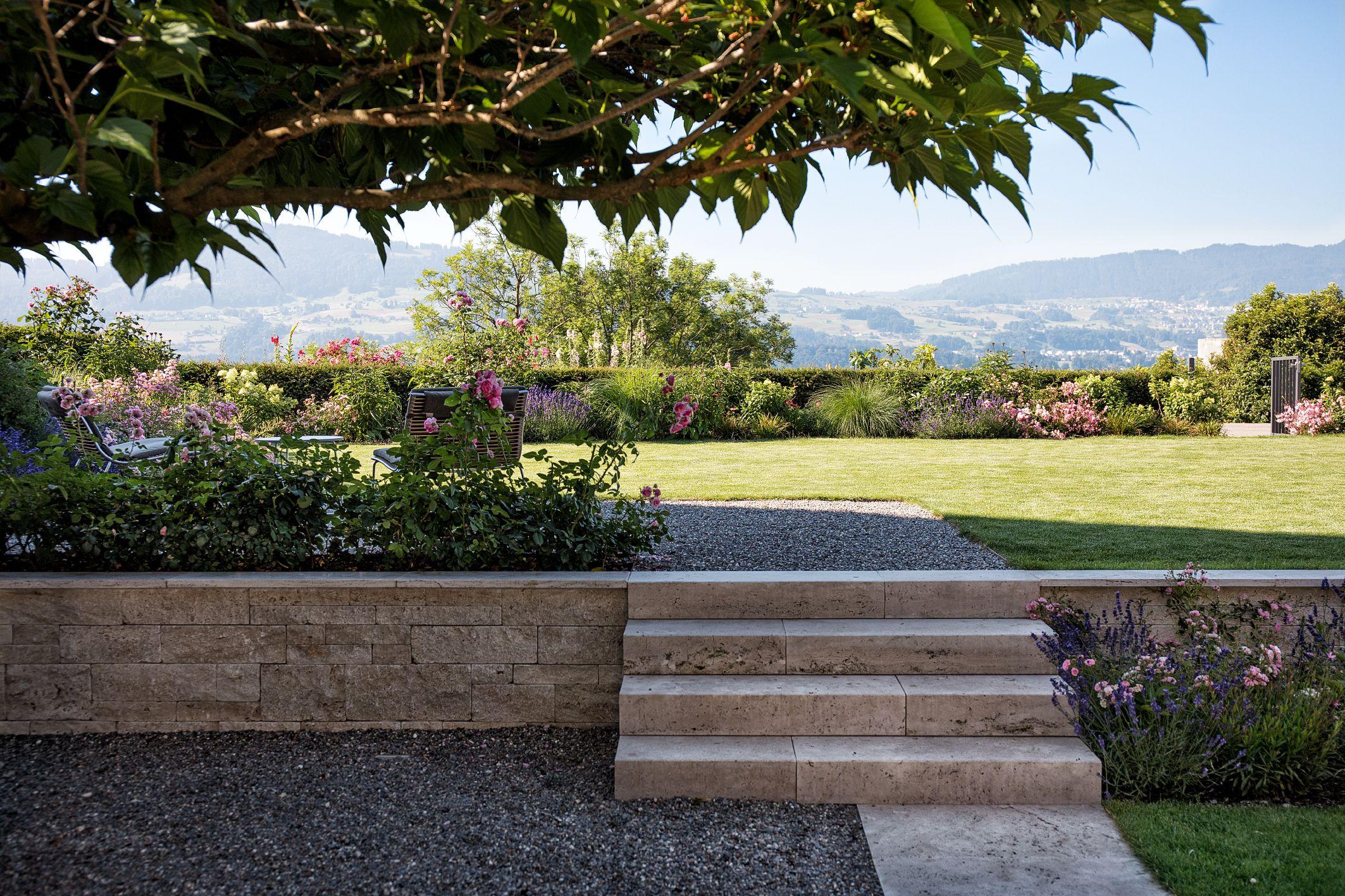 Die Niedrige Mauer Die Zugleich Eine Stutzfunktion Ubernimmt Wird Zum Blickfang In Diesem Traumgarten Die Treppe Fuhrt A Garten Traumgarten Gartengestaltung