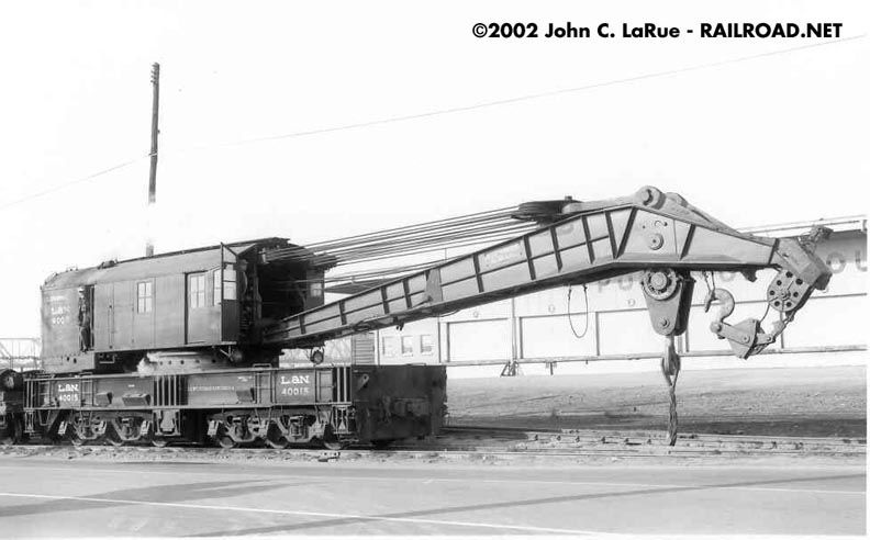 """L&N 40015. This 250-ton Bucyrus-Erie machine represents the ultimate size and capacity of the railroad wrecking derrick. Though normally stationed at the L&N's South Louisville Shop, it is seen here along the Louisville waterfront, apparently en route to a derailment on the """"river line"""", a branch serving industries along the Ohio River. The wrecker eventually met its end in a scrap yard behind the photographer."""