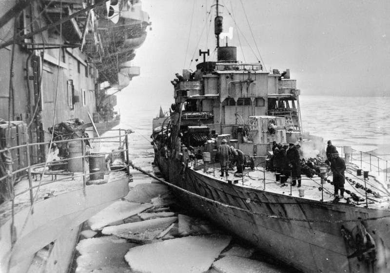 HMS Honeysuckle coming alongside the aircraft carrier HMS Trumpeter in the ice pack (Convoy to Russia).