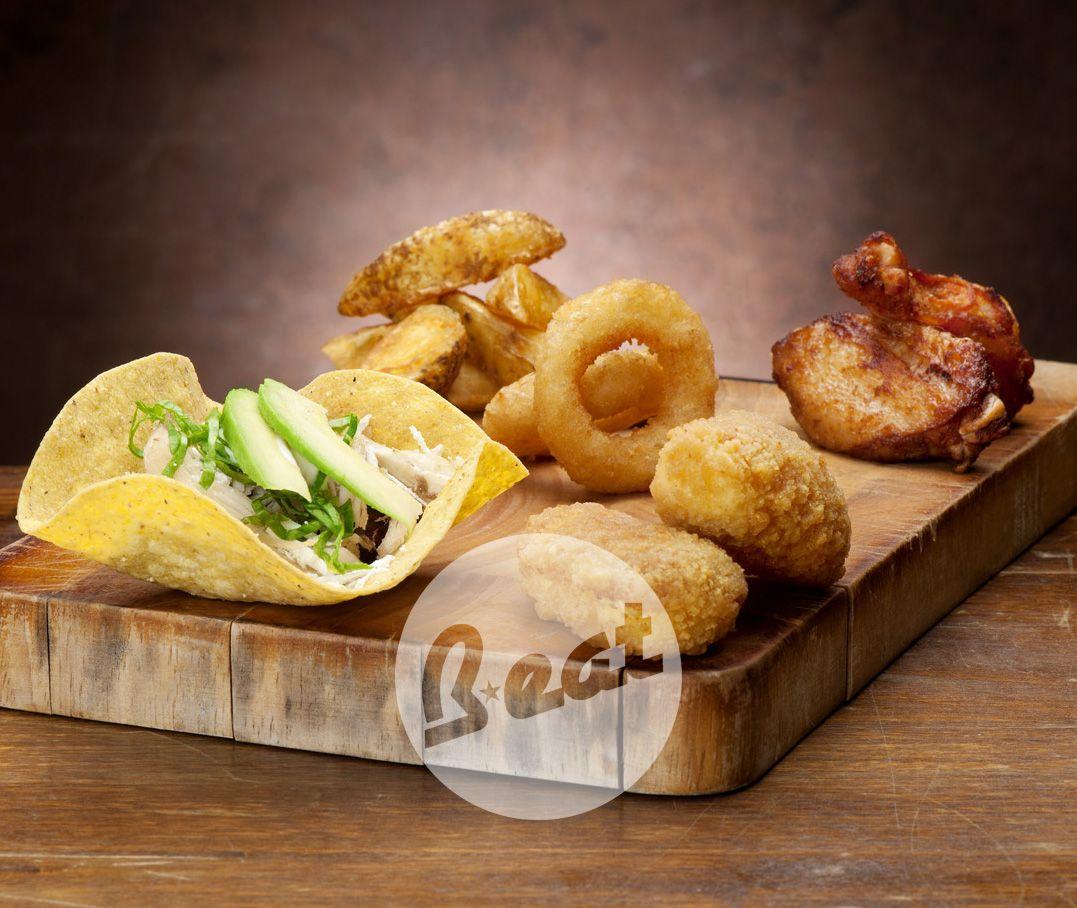 WEST COAST: Antipasto misto con alette di pollo, jalapenos Red Hot o Green, onion ring, tostada (tortilla di mais fritta, riempita di crema di fagioli, pollo sfilacciato, formaggio, insalata, panna acida e fetta da avocado), American fries