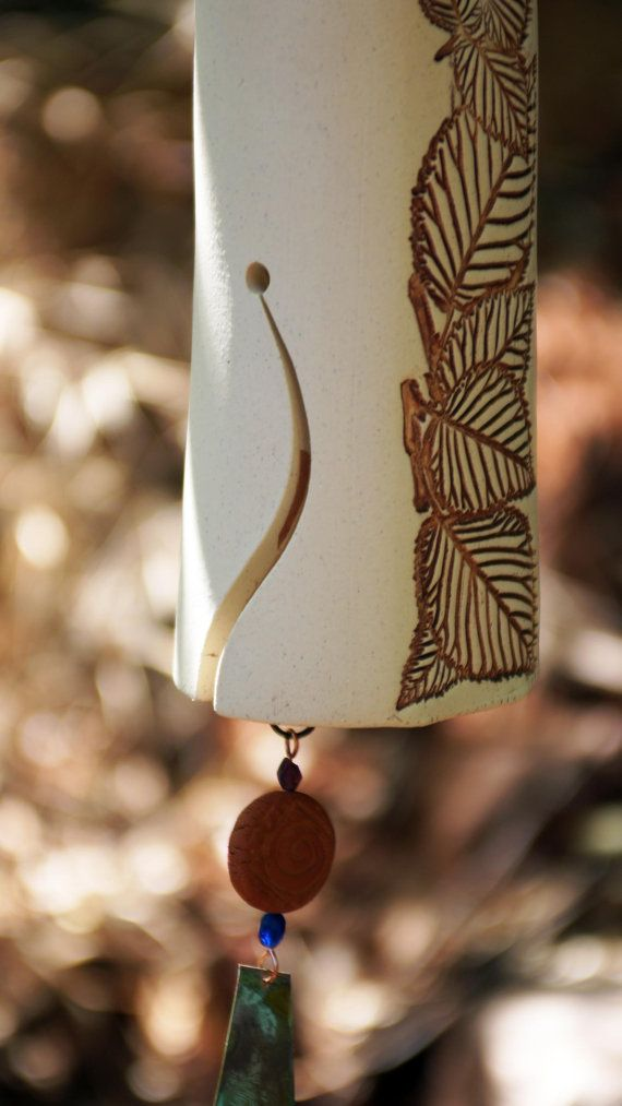 This handmade, white ceramic wind chime features a beautiful carved pattern of leaves, accented by a large copper wind-sale with a patina finish. A small clay bird sits atop. My wind chimes serve so many purposes, besides just beautiful garden décor. They alert you to the severity of the wind that day, will scare off birds and animals that you don't want in your garden, and will create a peaceful, zen-like sound for the outdoors with its wooden clapper (hear their sound on the YouTube clip…