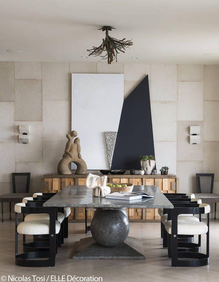 Une grande table contemporaine entourée de fauteuils en cuir l