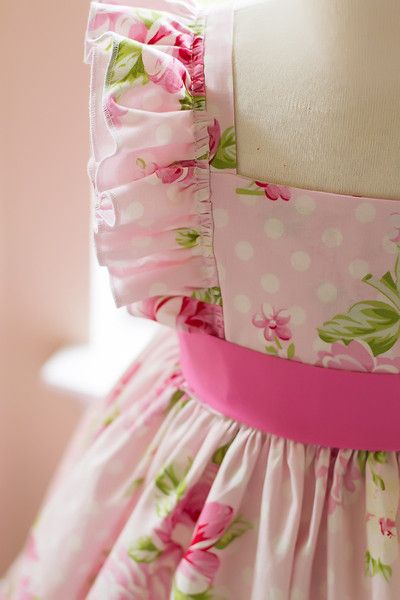 Evelyn is a gorgeous pink girls handmade floral dress. This vintage style inspired pattern is full of beautiful details such as flutter sleeves, a solid pink sash, and a classic style bodice that butt