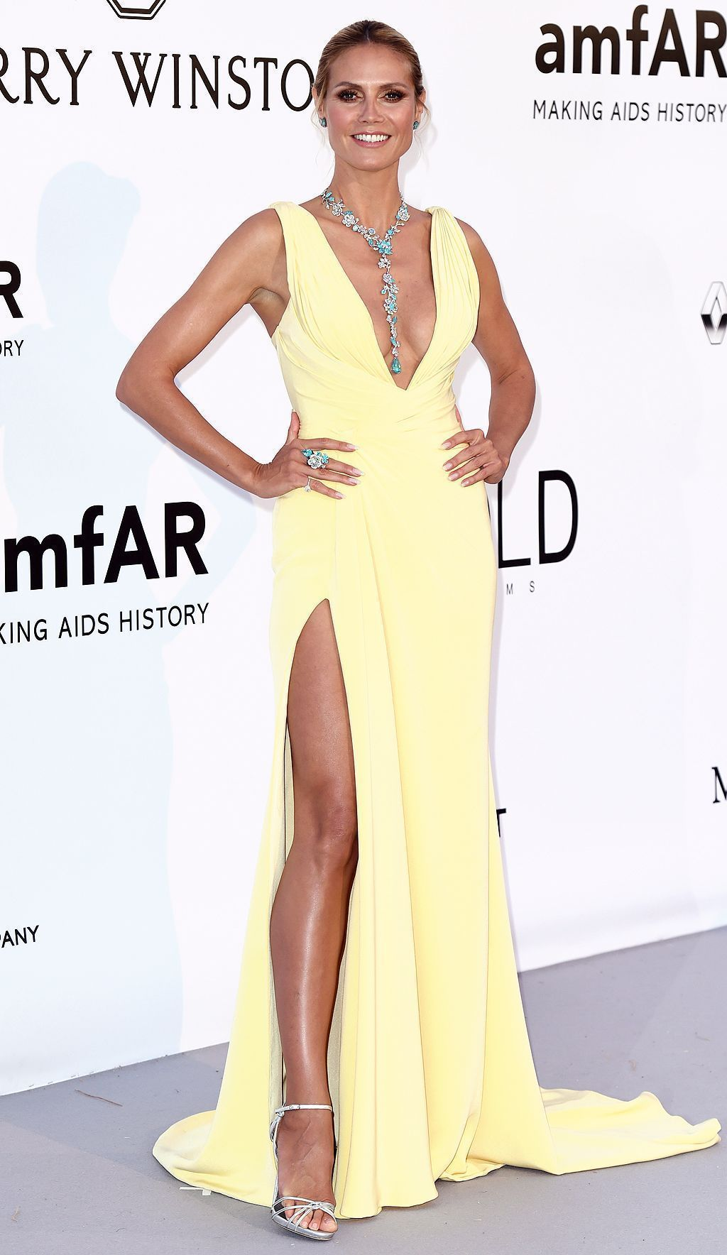 Heidi klum wears a pale yellow gown that showcases her assets u and