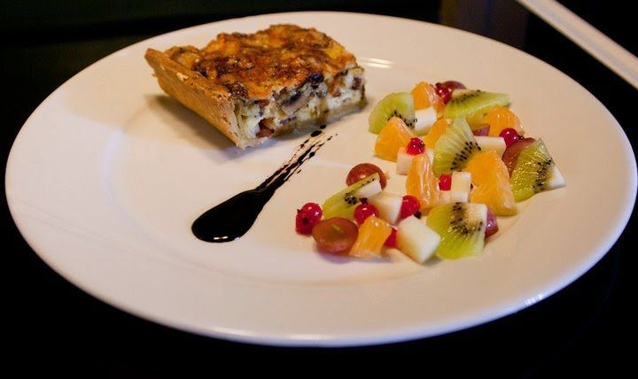 Quiche Lorraine with a fruit salad and a balsamic reduction
