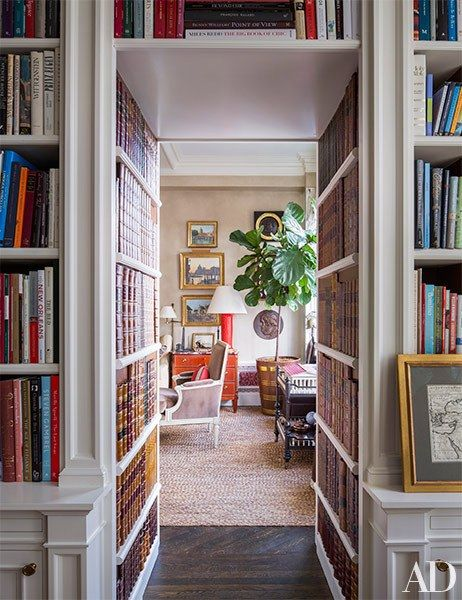 A wall lined with bookshelves leads into the living room for Casa moderna hampton hickory